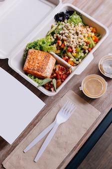 Caixa de refeição de comida limpa: filé de salmão grelhado com salada de tomate e broto de feijão.