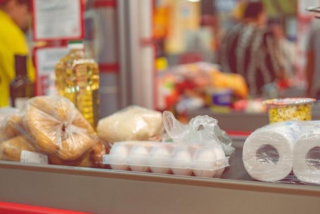 Caixa de supermercado com comida na esteira para compra no fim de semana