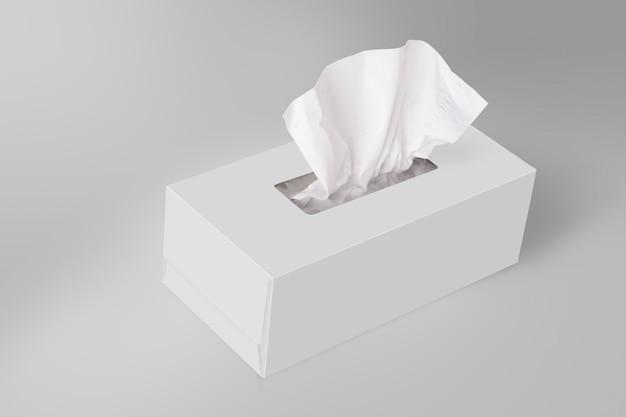 Caixa de tecido branco em branco sobre fundo cinza com tecido facial