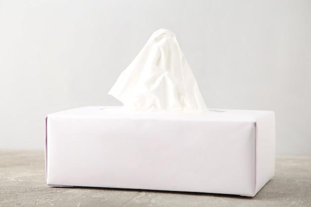 Caixa de tecido branco em fundo cinza.