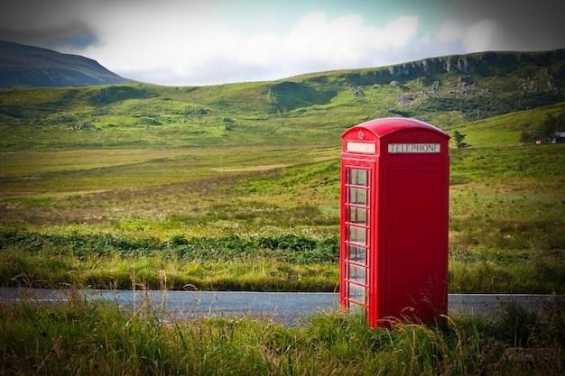 Caixa de telefone inglesa vermelha típica em uma área rural perto de uma estrada.