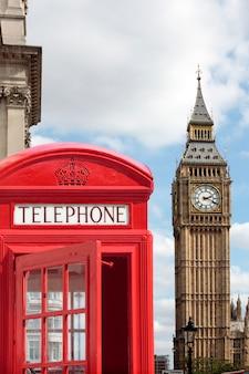 Caixa de telefone vermelha tradicional com big ben fora de foco no fundo.