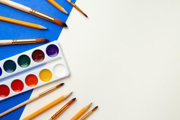 Caixa de tinta aquarela e conjunto de pincéis na vista superior do fundo azul e branco
