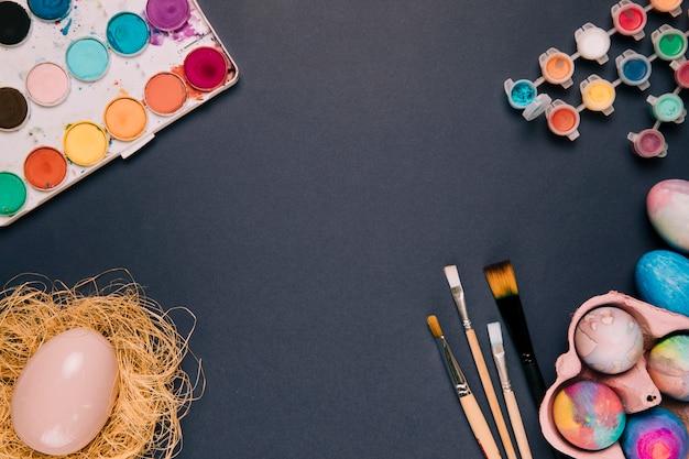 Caixa de tinta aquarela e garrafa de plástico; ovos de pascoa; pincéis em fundo preto