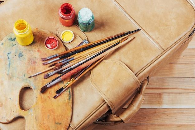 Caixa de tintas aquarela, pincéis de arte em tela.