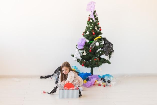 Caixa de transporte infantil surpresa com lixo de plástico sobre a árvore de natal