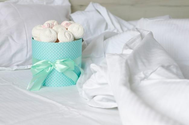 Caixa de turquesa com fita cheia de merengues em um lençol de cama branca.