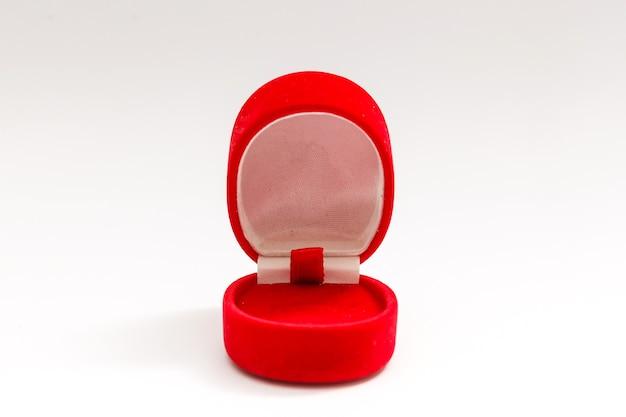 Caixa de veludo vermelha para o anel, aberta, isolada sobre o fundo branco