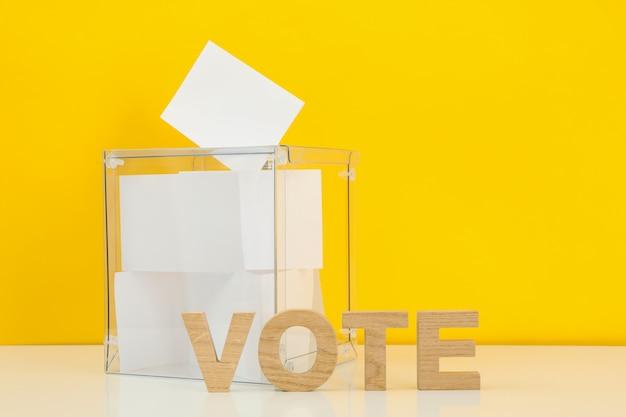 Caixa de votação com boletins e texto vote na superfície amarela