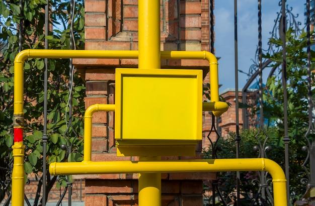 Caixa do medidor de gás amarela com tubos e válvulas ao ar livre. caixa metálica antivandálica, equipamento a gás. copie o espaço para o texto.