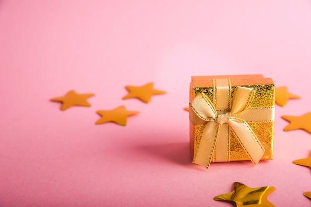 Caixa dourada com um presente. confetes de estrelas douradas.