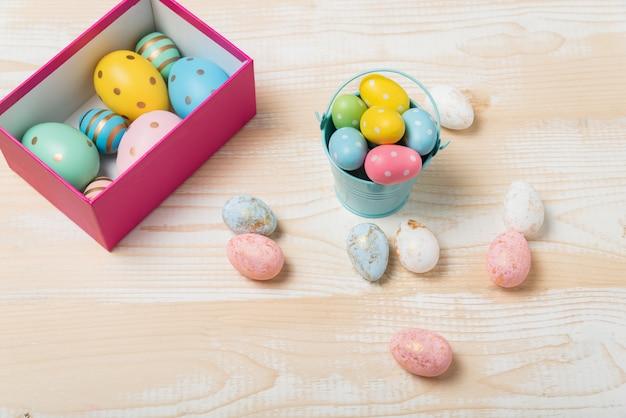 Caixa e balde com ovos de páscoa coloridos. fundo de madeira