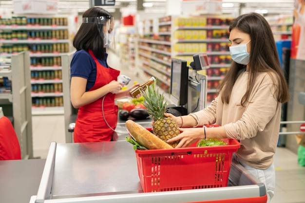 Caixa e cliente do supermercado seguindo as regras de proteção pessoal durante os dias de quarentena do coronavírus, usando máscaras