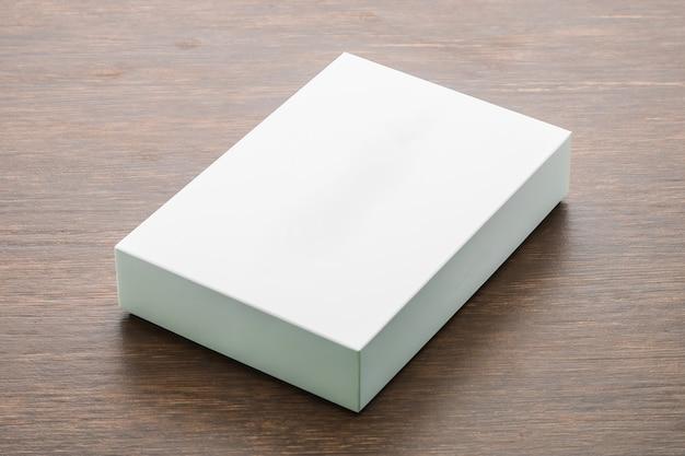 Caixa em branco simulada acima no fundo de madeira