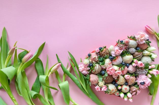 Caixa em forma de coração com morangos cobertos de chocolate artesanais com diferentes coberturas e flores como presente no dia dos namorados em fundo rosa com espaço livre para texto