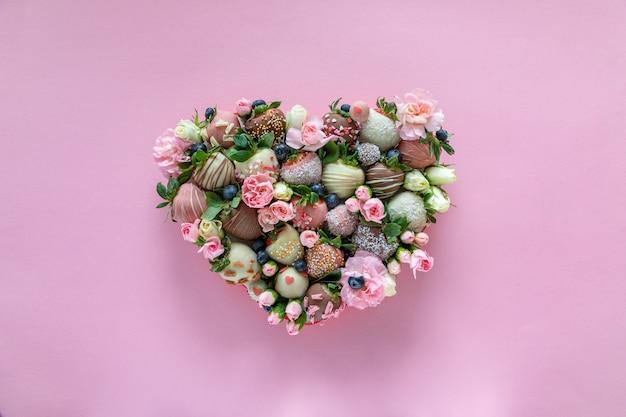 Caixa em forma de coração com morangos cobertos de chocolate artesanais com diferentes coberturas e flores como presente no dia dos namorados em fundo rosa