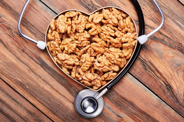 Caixa em forma de coração com nozes. estetoscópio em pano de fundo de madeira. minha profissão é médica.