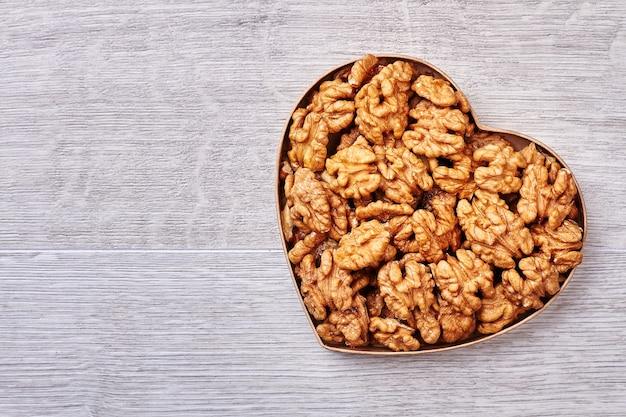Caixa em forma de coração com nozes. nozes descascadas em fundo de madeira. alimentos saudáveis para obter energia.