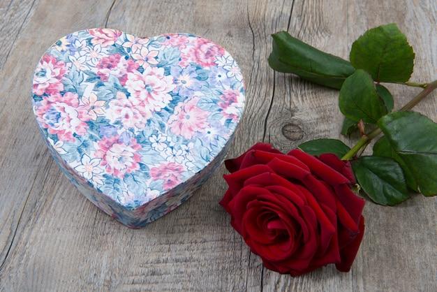 Caixa em forma de coração com uma rosa vermelha
