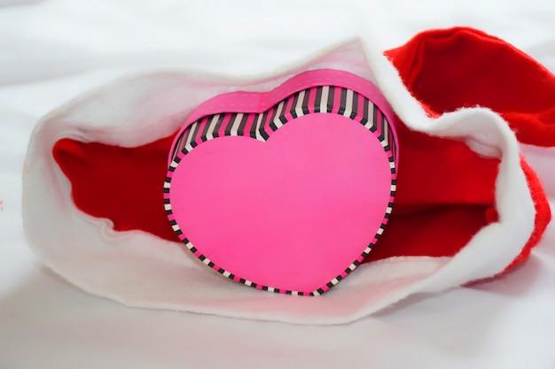 Caixa em forma de coração dentro de um chapéu de papai noel