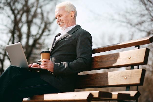 Caixa externa. ângulo baixo do empresário maduro e alegre usando o laptop enquanto segura o café
