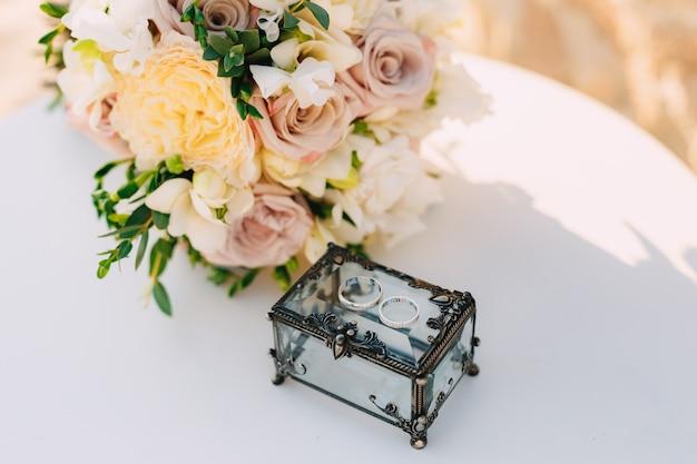 Caixa fechada com metal forjado e anéis de ouro para os noivos em uma mesa branca com um buquê