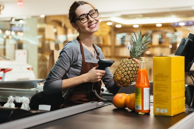 Caixa feminina feliz digitalização itens de mercearia
