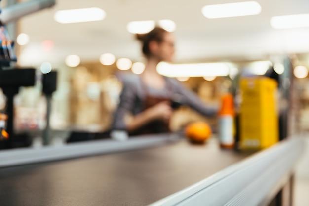 Caixa feminina jovem, digitalização de itens de mercearia