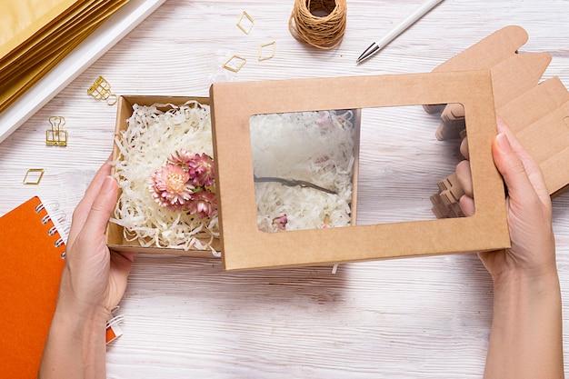 Caixa marrom com dobra de papel shred filler na mesa de madeira