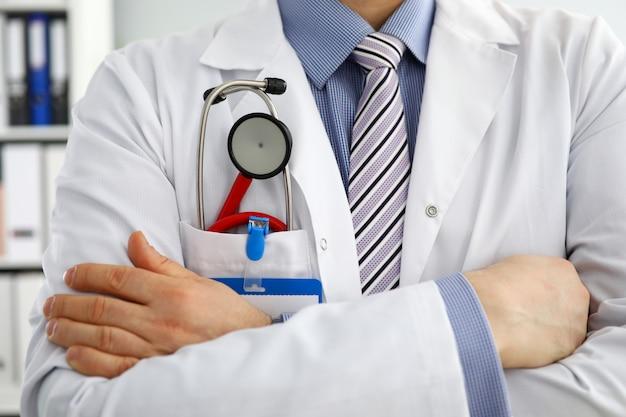Caixa masculina do doutor do therapeutist da medicina com o estetoscópio no close up do bolso. instrumentos e ferramentas médicas compram física e prevenção de doenças exame do paciente