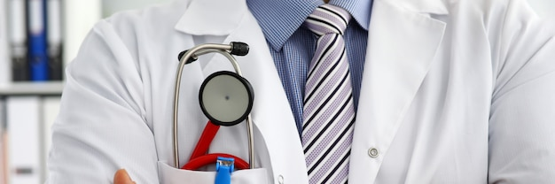 Caixa masculina do doutor do therapeutist da medicina com o estetoscópio no close up do bolso. instrumentos e ferramentas médicas compram o conceito de estilo de vida saudável do exame 911 do paciente para prevenção de doenças e doenças
