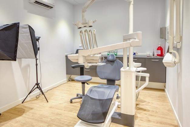 Caixa moderna clínica odontológica totalmente equipada, com paredes brancas e piso de madeira