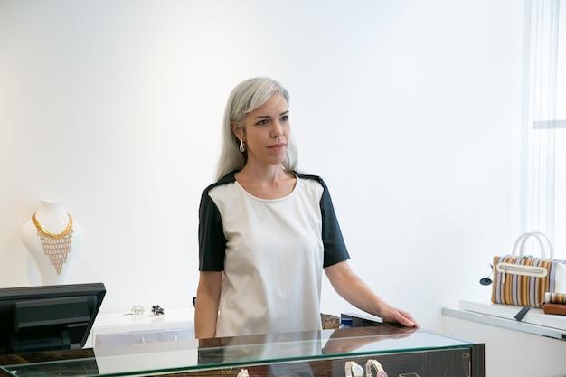 Caixa ou vendedor da loja trabalhando em uma butique moderna, em pé na mesa com a caixa registradora e olhando para o outro lado. tiro médio. loja de varejo ou conceito de trabalho