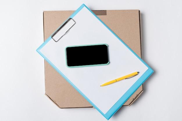 Caixa, papéis, caneta e smartphone na vista superior do fundo branco. encomende pizza através de um aplicativo, entrega em domicílio