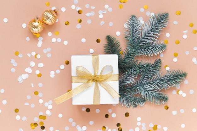 Caixa para presente de natal ou ano novo em fundo bege com bolas coloridas de confete ouro e abeto