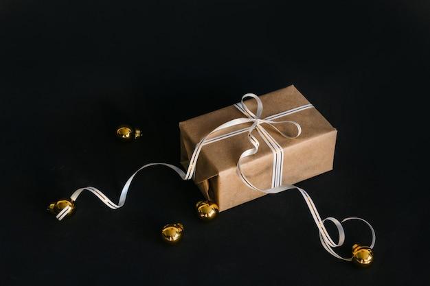 Caixa para presente embrulhada em papel reciclado e amarrada com um laço de fita branca e dourada sobre fundo preto, ao lado das bolas douradas de natal da árvore. surpresa para o feriado.