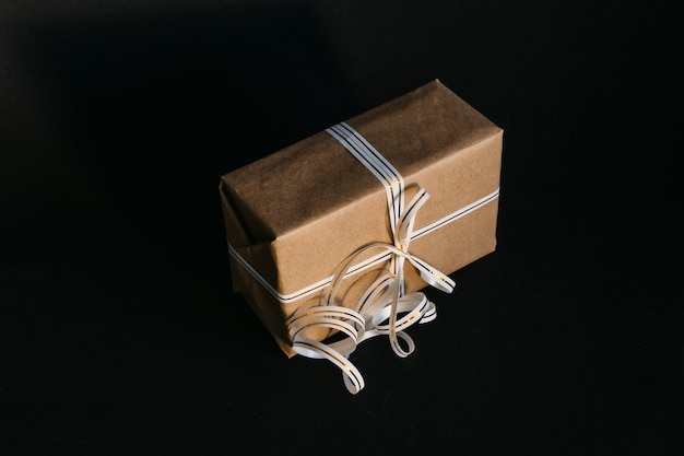 Caixa para presente embrulhada em papel reciclado e amarrada com um laço de fita branca e dourada sobre fundo preto. surpresa para o feriado.