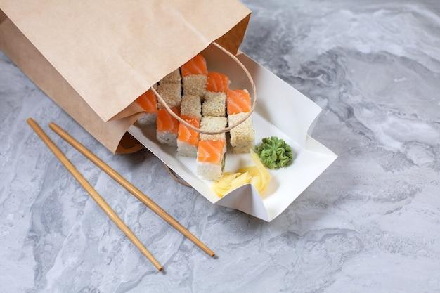 Caixa para viagem com rolos de sushi em saco de papel pardo.