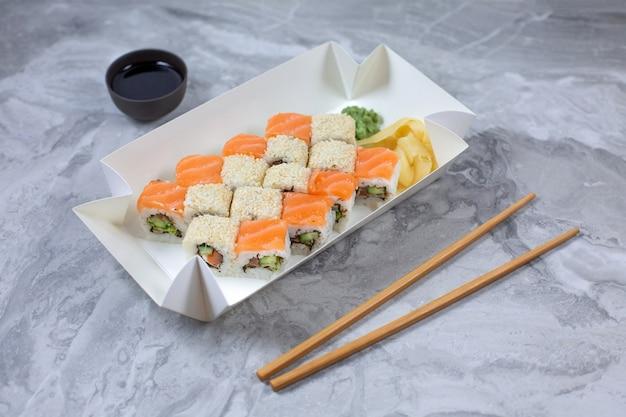 Caixa para viagem com sushi rola na mesa de pedra.