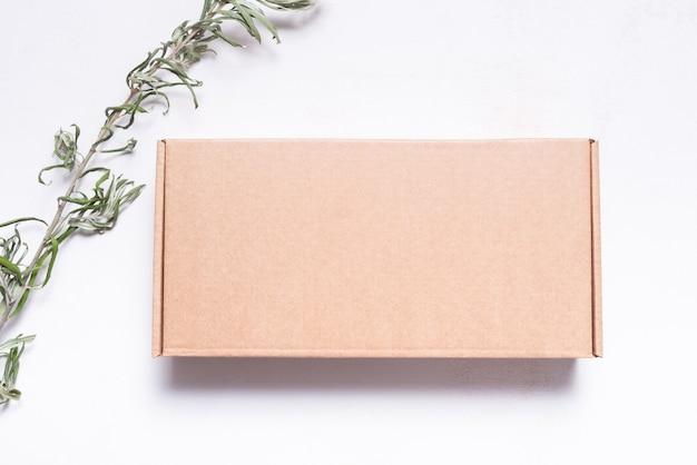 Caixa postal de papelão marrom decorada com folhas secas