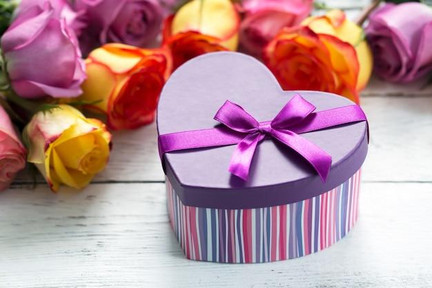 Caixa presente na frente, rosas roxas e amarelas