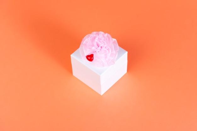 Caixa quadrada branca em uma laranja com um laço rosa e coração pequeno vermelho