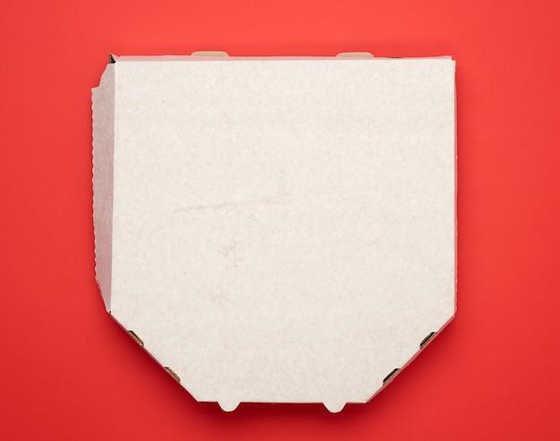 Caixa quadrada de papelão branca para pizza em fundo vermelho