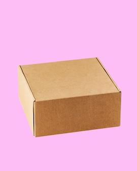 Caixa quadrada de papelão kraft fechada, a caixa é esculpida em um fundo rosa