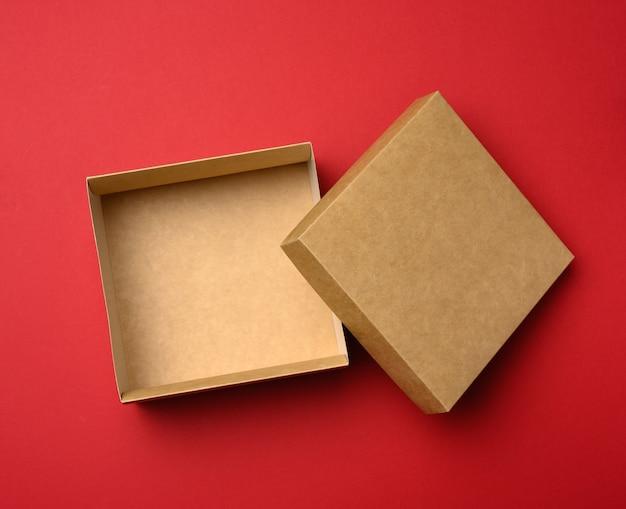 Caixa quadrada marrom vazia em um fundo vermelho, presente aberto, vista superior