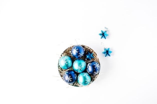 Caixa redonda com bolas de natal azuis brilhantes sobre fundo branco.