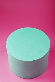 Caixa redonda em fundo rosa para presente.