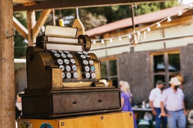 Caixa registradora dourada vintage à venda em um mercado de antiguidades