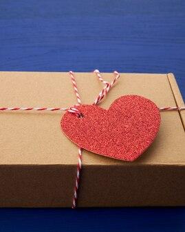 Caixa retangular marrom com um presente e um coração de papel vermelho amarrado a uma corda