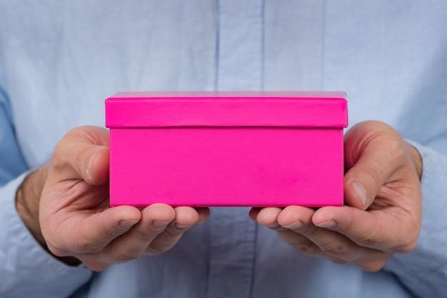 Caixa rosa nas mãos dos homens. o homem dá um presente